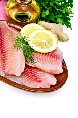 Tilapia fillets with dill, parsley and lemon in a clay pot, a bottle of vegetable oil, ginger, pink napkin isolated on white background photo