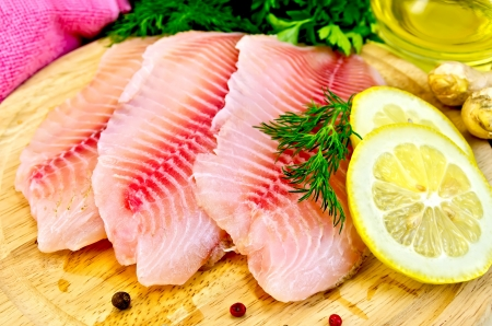 Tilapia fillets with dill, parsley, lemon, a bottle of vegetable oil, ginger, pink cloth, bell pepper on a wooden board