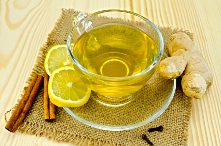 Ginger tea in a glass cup, two slices of lemon, cinnamon, cloves, ginger root on a napkin of burlap and wooden board Standard-Bild