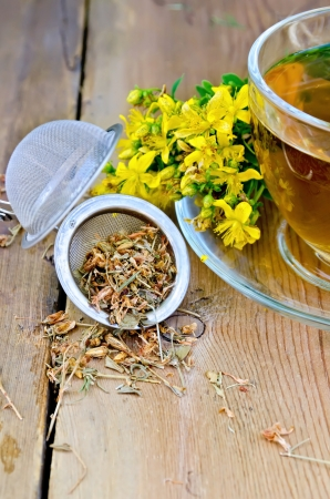 Metal tea strainer with dry flowers tutsan, fresh flowers of Hypericum , tea in a glass cup on a wooden boards background