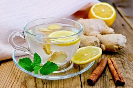Ginger tea in a glass cup, lemon, cinnamon, ginger, mint, napkin against a wooden board