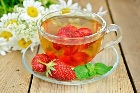 Tea with strawberries in a glass cup, mint, a bouquet of camomiles on a background of wooden boards photo