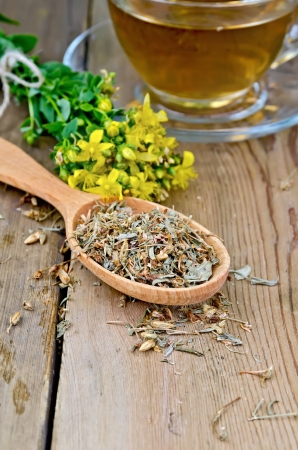 Wooden spoon with dried flowers tutsan, a bouquet of fresh flowers tutsan, glass cup with tea on a wooden boards background photo