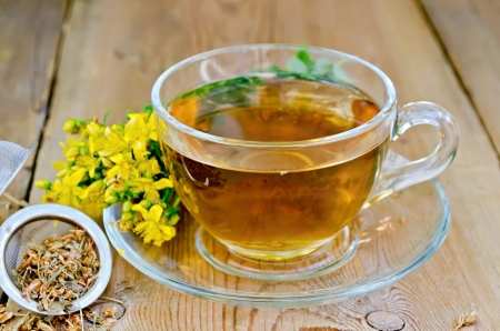 tea filter: Tea in a glass cup, a metal filter for tea with dried flowers tutsan, Hypericum fresh flowers on the background of wooden boards Stock Photo