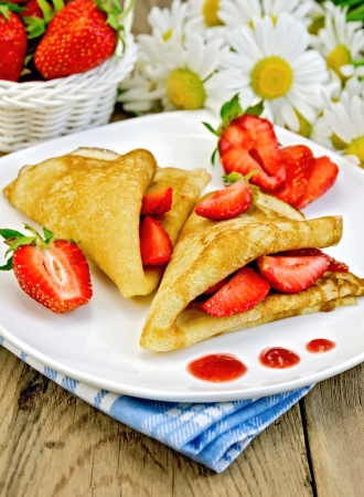 rubicund: Two pancakes with strawberries and jam on a white plate, basket with berries, bouquet of daisies on a background of wooden boards