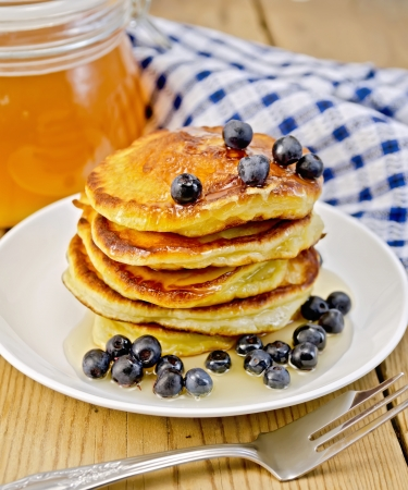 A stack of pancakes with blueberries and honey on a white plate, a jar of honey, a napkin on a background of wooden boards Stock Photo