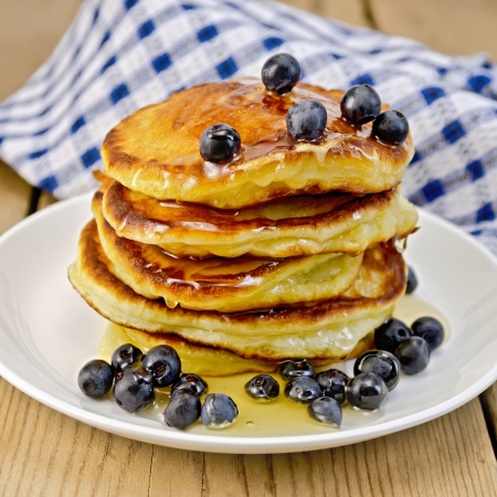 rubicund: A stack of pancakes with blueberries and honey on a white plate, napkin against a wooden board