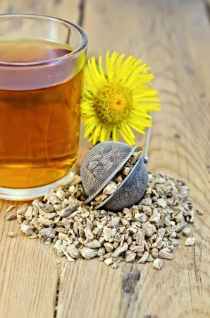 expectorant: Metal sieve with elecampane root, fresh yellow flower elecampane, tea in glass mug on a background of wooden boards