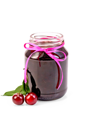 Cherry jam in a glass jar, two cherries on a branch with leaves isolated on white background photo