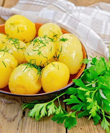 Boiled potatoes with dill, drizzled with oil in a crockery, a bunch of parsley, a napkin on a wooden boards background photo