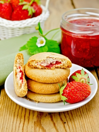 Stack of cookies filled with jam and strawberries on a plate, a jar of strawberry jam, a wicker basket with a strawberry on wooden board photo