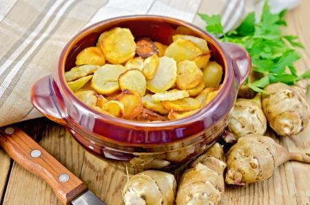 Jerusalem artichoke roasted in a clay pot, a bunch of parsley, fresh artichoke tubers, napkin, knife on background wooden board