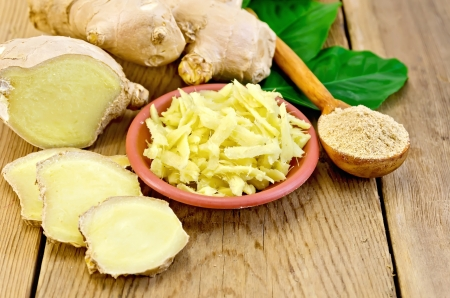 Brown dish with grated ginger, a wooden spoon with powder, ginger root, green leaves on the wooden board Standard-Bild