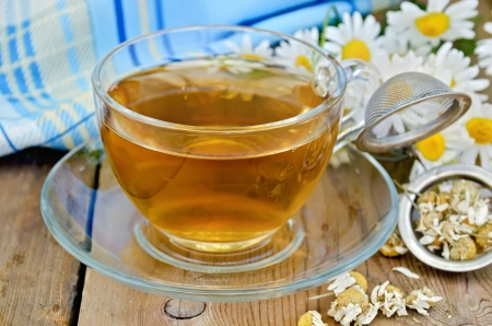 strainer: Herbal tea in a glass cup, a metal strainer with dried chamomile flowers, a bouquet of fresh chamomile flowers, napkin against a wooden board Stock Photo