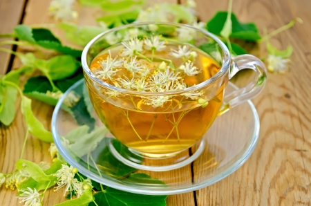 Herbal tea in a glass cup, fresh linden flowers on a background of wooden boards photo