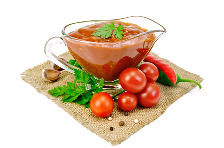 Ketchup in a glass sauceboat with tomatoes and parsley, hot pepper, garlic on a sacking isolated on a white background photo