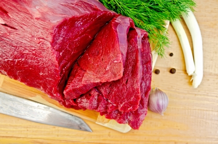 A piece of beef, garlic, peas pepper, dill, chives, knife on a wooden board photo