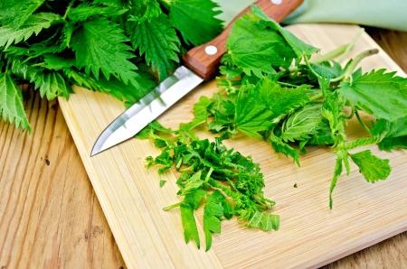 tovagliolo: Fresco verde ortica incisa su una tavola di legno con un coltello e tovagliolo