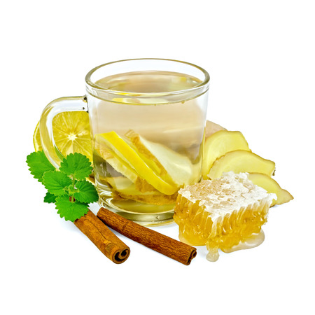 Ginger tea with lemon in a glass mug, mint, cinnamon, ginger root, honeycomb isolated on white background photo