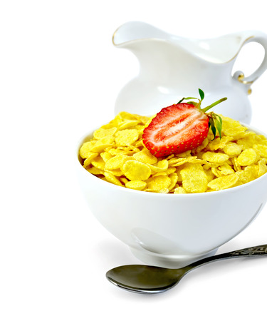 Cornflakes in a white bowl with strawberries and milk in a jug, a spoon isolated on white  photo