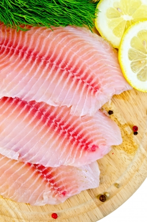 Tilapia fillets with dill, lemon and pepper on a wooden board isolated on white  photo