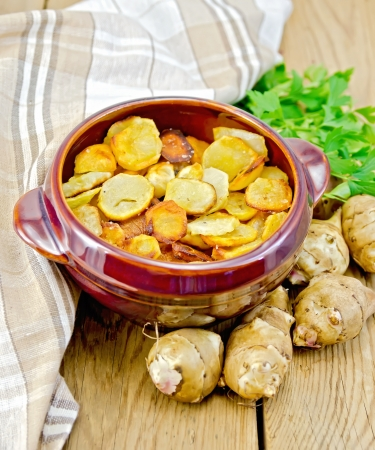 jerusalem artichoke: Jerusalem artichokes roasted in a clay pot, parsley, fresh artichoke tubers, napkin on a wooden board