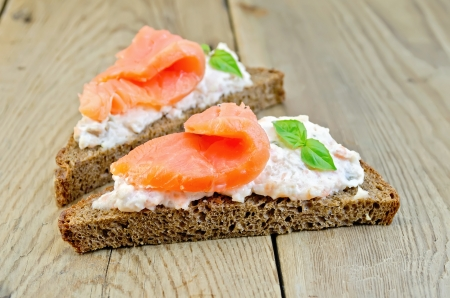Toast two slices of rye bread with cream, basil and salmon on the wooden boards photo