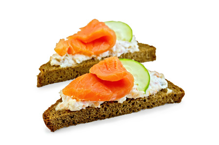 Toast two slices of rye bread with cream, salmon and cucumber isolated on white background photo