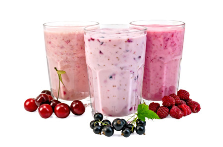 Milk shakes with berries of black currant, cherry, raspberry in glass isolated on white background Stock Photo