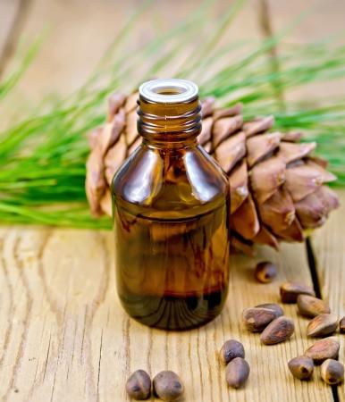 Cedar oil in a bottle, cedar cone, cedar nuts on the background of wooden boards