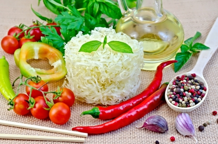 Rice noodles twisted, tomatoes, different pepper, oil in carafe, chopsticks, garlic on a background of sack cloth photo
