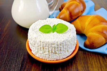 cagliata: Curd in ceramica con basilico, due bagel, una brocca di latte, tovagliolo sulla tavola di legno Archivio Fotografico
