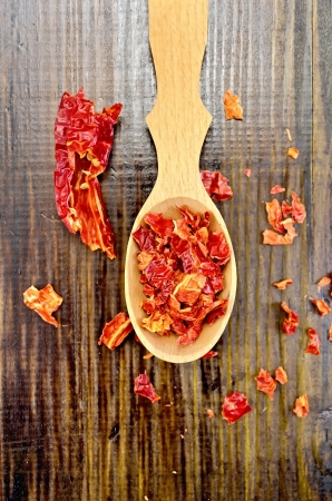 pepper flakes: Red pepper flakes in a wooden spoon and a pod of dry red pepper on a wooden board on top Stock Photo