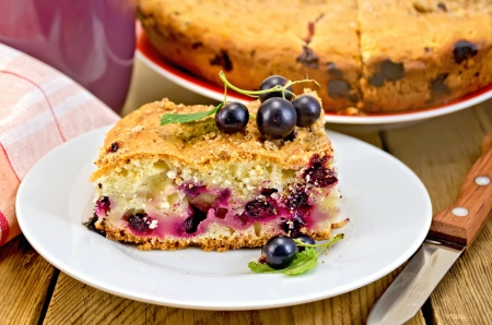 Sweet piece of cake with black currant, napkin, cup, knife on wooden plank Stock Photo