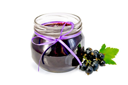 Glass jar with black currant jam, twigs with berries and leaves of black currant isolated on white