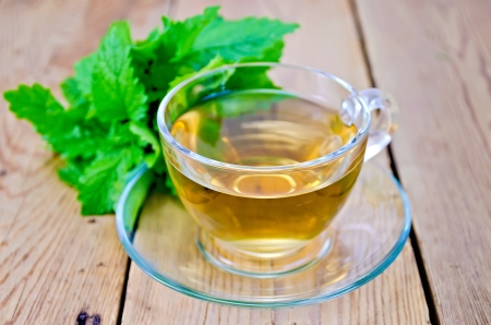 Herbal tea in glass cup, fresh melissa leaves on the background of wooden boards