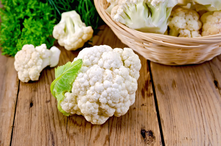 Cauliflower on a table and in a wicker basket, dill, parsley on wooden board Archivio Fotografico