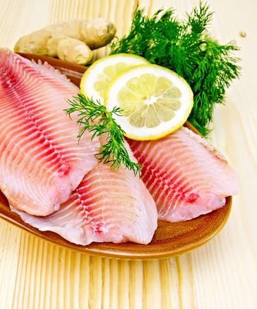Tilapia fillets with lemon and dill in pottery, ginger root on the background of wooden boards Archivio Fotografico