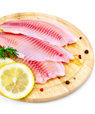 Tilapia fillets with dill, lemon slices, peppercorns on a wooden board isolated on white background