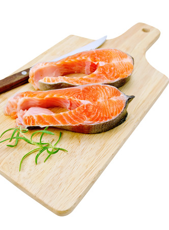 Two pieces of trout with rosemary and a knife on a wooden board isolated on white background photo