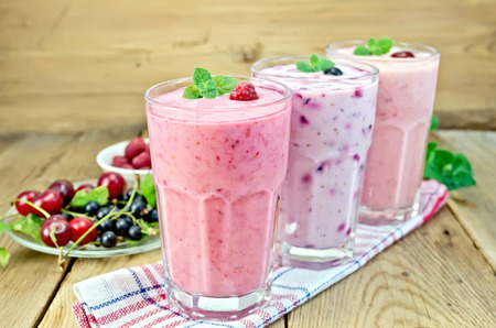 Milkshakes with black currant, cherry, raspberry in glass on the background of wooden boards photo