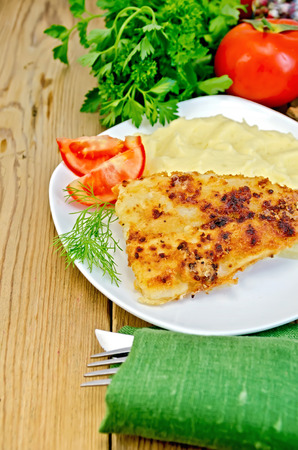 Fried fish with mashed potatoes on a plate, parsley, tomatoes, napkin, knife and fork on a wooden board photo
