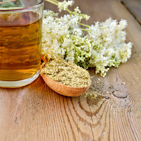 Wooden spoon with dried flowers, a bouquet of fresh flowers of meadowsweet, tea in glass mug on the wooden boards photo