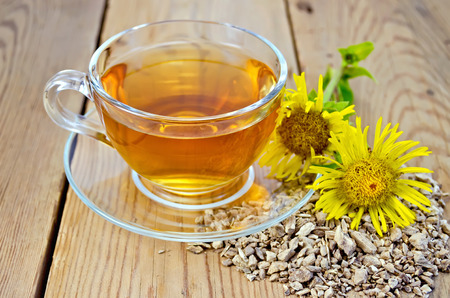 expectorant: Elecampane root, fresh yellow flower elecampane tea in a glass cup on a wooden board