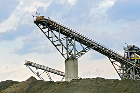 Equipment for the production of crushed stone on a background of blue sky and clouds photo