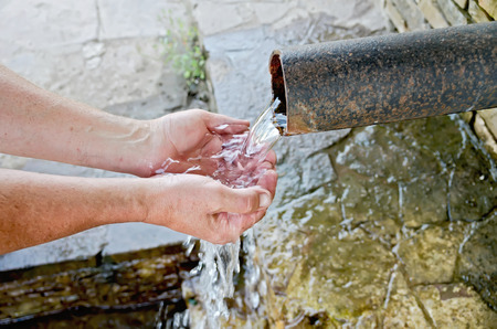 Spring water flows from the pipe into the hands of the men on the background of stone photo