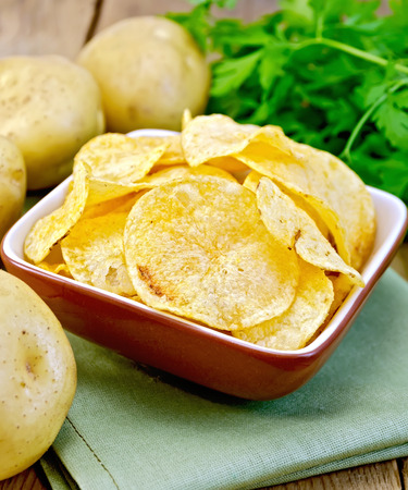 Potato chips in a clay bowl on a napkin, fresh potatoes, parsley on a wooden boards background photo