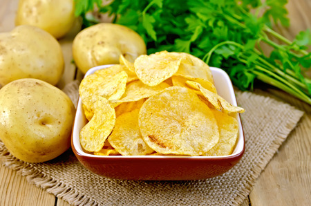 Potato chips in a clay bowl on a napkin from a burlap, fresh potatoes, parsley on a wooden boards backgroun photo