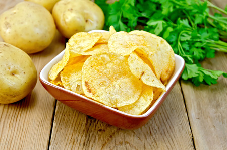 Potato chips in a clay bowl, fresh potatoes, parsley on a wooden boards background photo