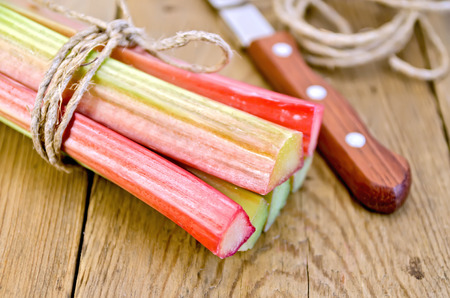 Bundle of stalks of rhubarb with a knife and a coil of rope on the background of wooden boards photo